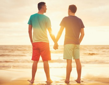 Happy gay couple watching sunset on the beach in st barths (saint barthelemy)